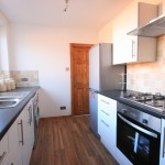 Newly fitted, high gloss kitchen with stainless/silver appliances